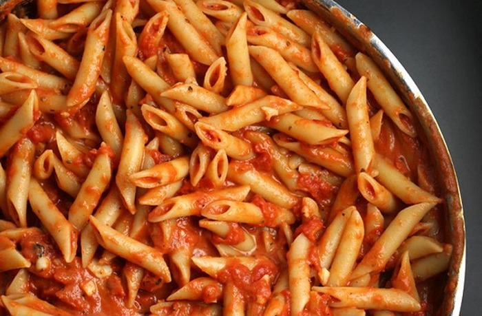 Pasta with onions and carrots in a pan